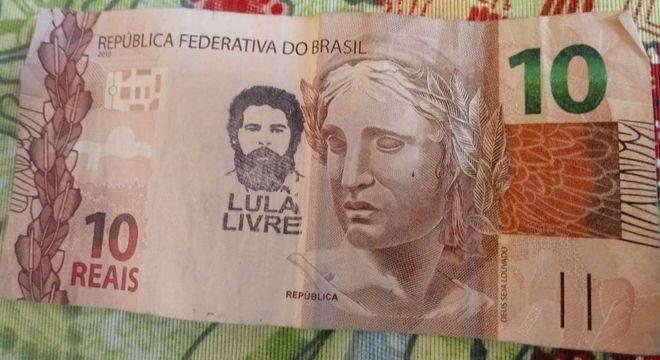 """Militantes Petistas Estão Vandalizando Nosso Dinheiro Carimbando Uma Imagem De """"Lula Livre"""" Em Vermelho Comunista."""